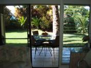 A102 - Lower lanai from living room through to fully landscaped grounds